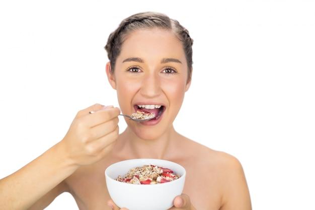 朗らかな健康的なモデルのシリアルを食べる