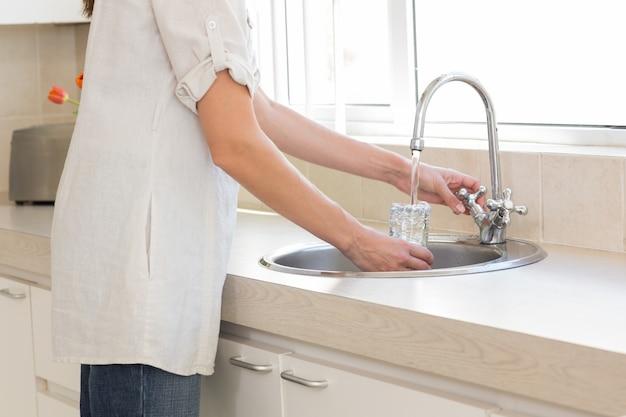 Середина разделе женщина мойка стекла в умывальник на кухне