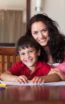 息子の宿題を助けてくれる喜びの母
