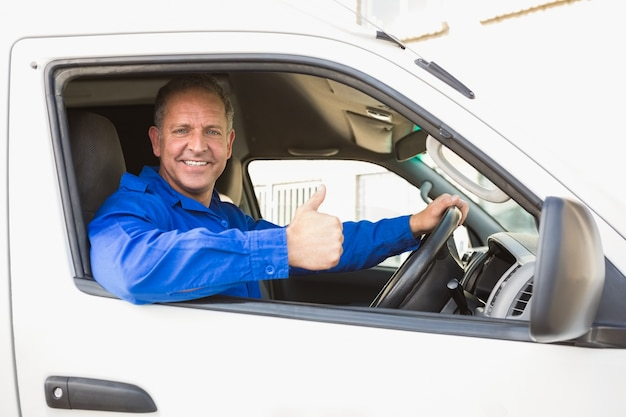 彼の車を運転している親指を示す配達ドライバー