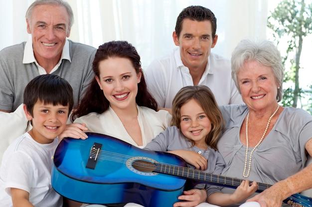Портрет семьи, держащей гитару в гостиной