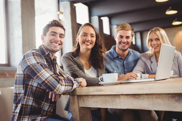 コーヒーを飲んでラップトップを使う笑顔の友人