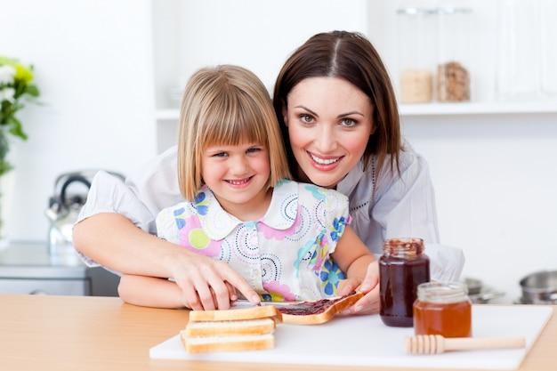 Внимательная мать помогает своей дочери готовить завтрак