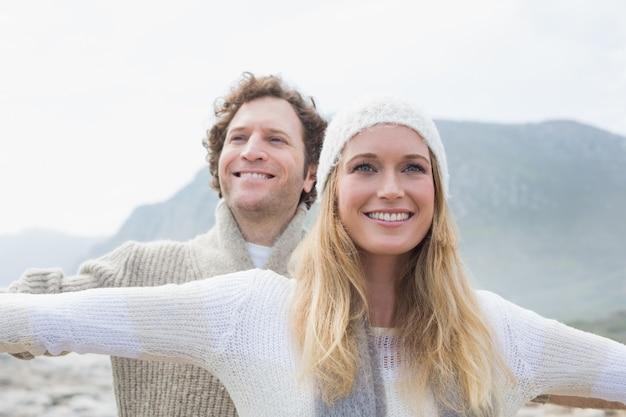 Повседневная молодая пара, протягивая руки на открытом воздухе