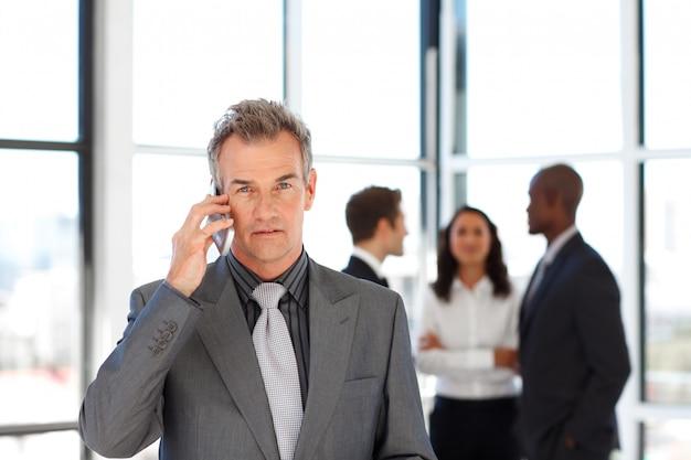 カメラを見て電話で熟練したビジネスマン