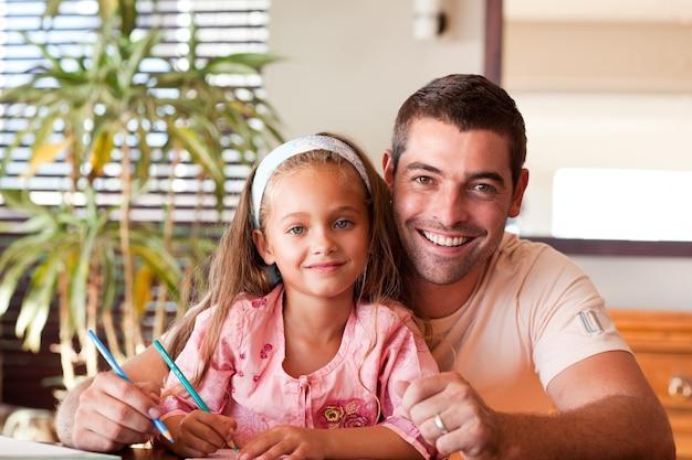 明るい父親が宿題のために娘を助ける