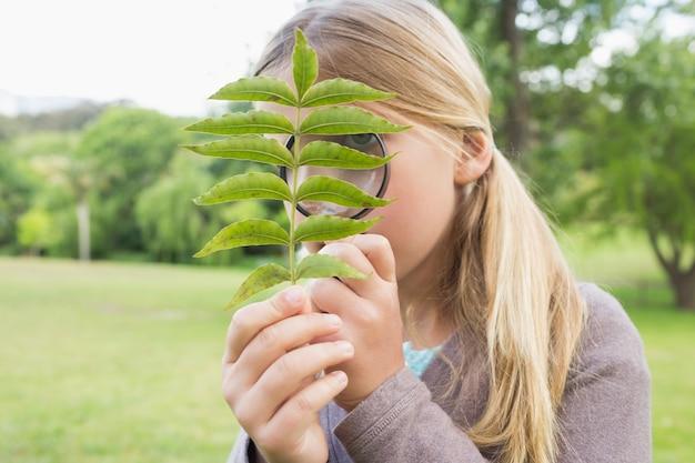 公園で虫眼鏡で葉を調べる少女