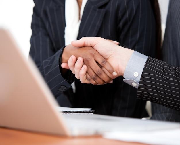 二つのビジネスマンとラップトップとの間の握手のクローズアップ