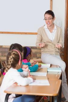 教室で若い生徒と話すかわいい先生
