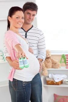 Веселая беременная женщина с детской обуви, в то время как муж касается ее живот в комнате их будущего ребенка