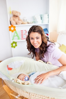 彼女の愛らしい赤ちゃんの世話をしている気配りの若い母
