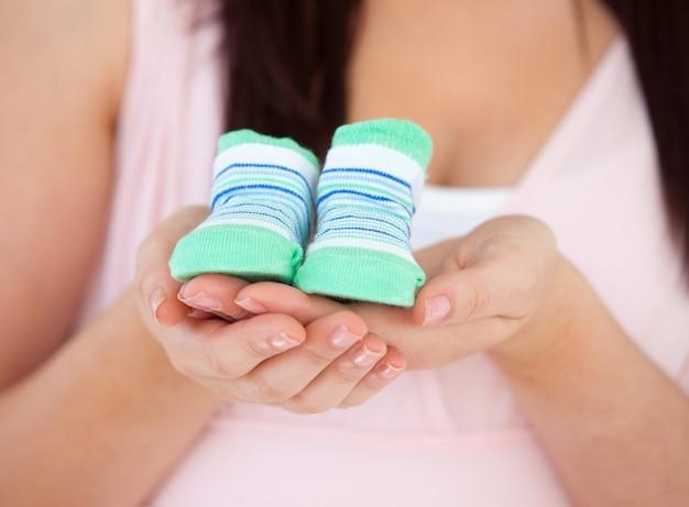 Крупный план беременная женщина с детской обуви