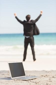 海の前で応援するハッピー・ビジネスマン