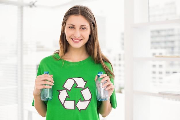 リサイクルボトルを持っている笑顔のエコなブルネット