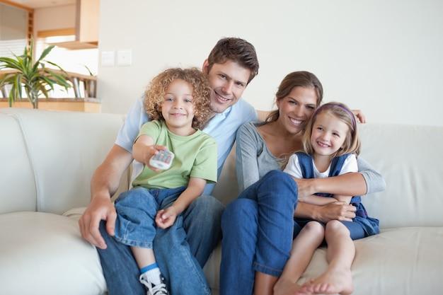 Улыбающаяся семья смотрит телевизор вместе