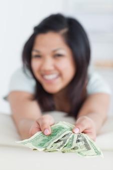 Женщина, держащая несколько долларовых купюр