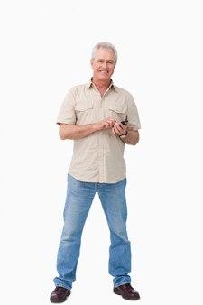 彼の携帯電話で成熟した男性を笑顔