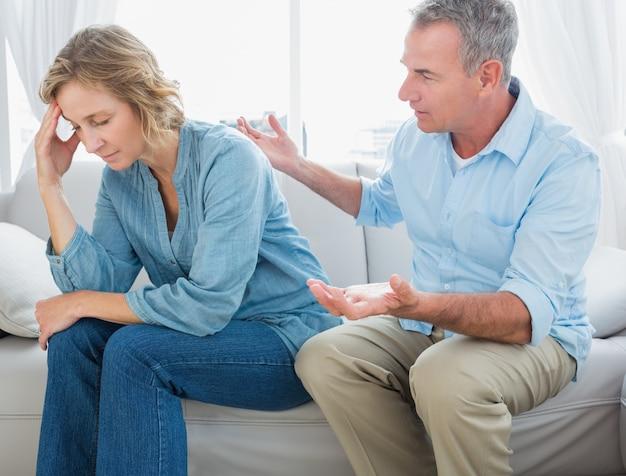 紛争のあるソファーに座っている中年のカップル