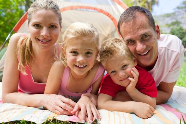 草の上に横たわっている幸せな家庭の肖像