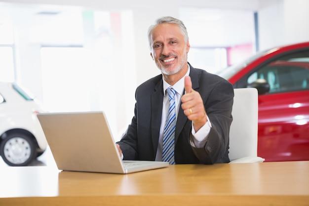 ラップトップを使って親指をあげている笑顔のビジネスマン