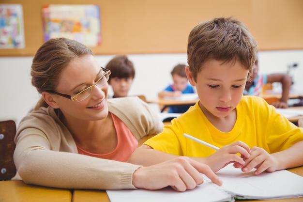 教室で生徒を助ける美しい先生