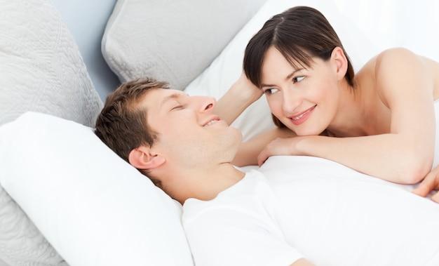 彼らのベッドに一緒に横たわっている幸せなカップル