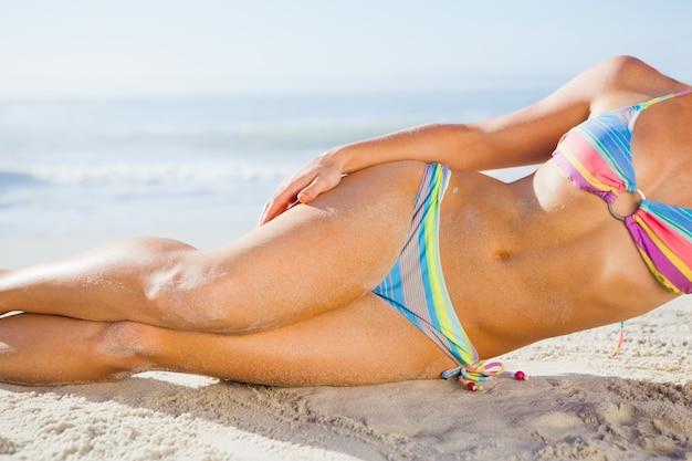 Великолепная женщина в бикини, лежа на пляже