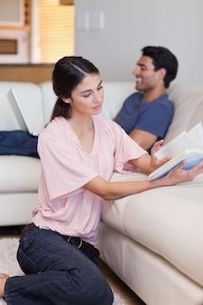 Портрет женщины, читающей книгу, пока ее жених использует ноутбук