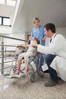 看護師がそれを押している車椅子の子供の隣にうずくくし博士