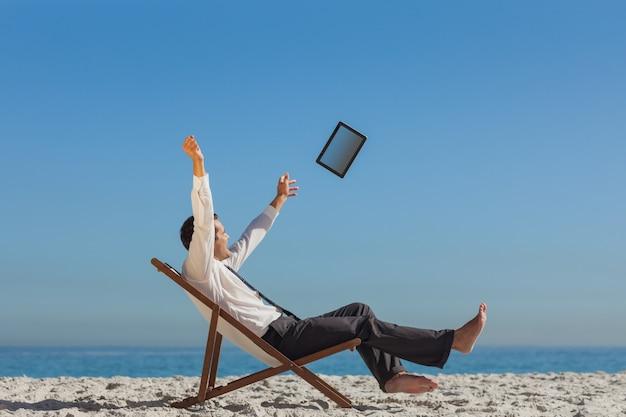 彼のデッキの椅子に勝利の若い実業家は、彼のタブレットを投げ捨てる
