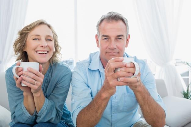 コーヒーを持つソファに座っているコンテンツ中年のカップル