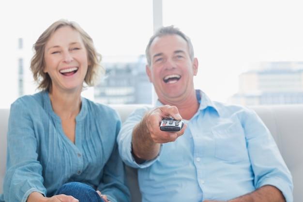 テレビを見てソファに座って中年のカップルを笑う