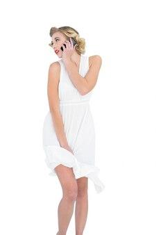 彼女の携帯電話で呼んでいる夢中のファッションブロンドモデル