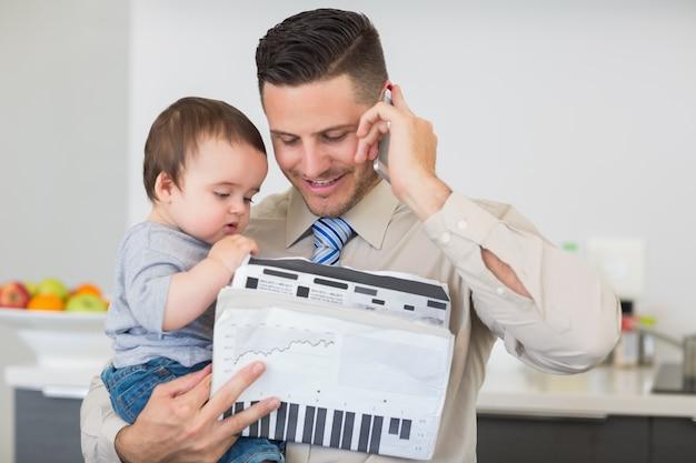 通話中に赤ちゃんを運ぶ書類を持つビジネスマン