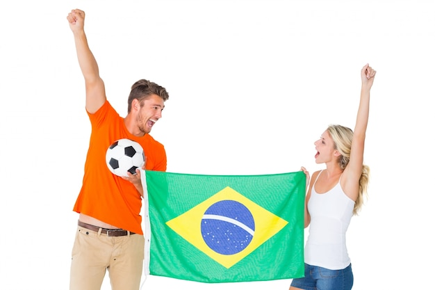ブラジルの旗を持っている興奮したサッカーファンのカップル