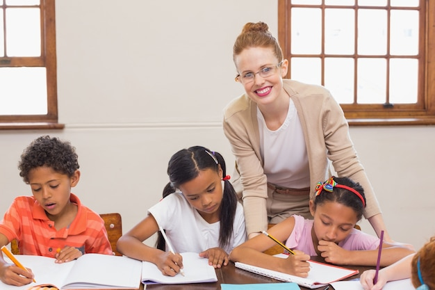 かわいい生徒が教室で先生から助けを得ている