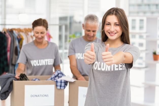 Улыбаясь женщина-волонтер, делая большие пальцы