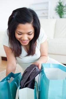 Женщина снимает одежду с сумки