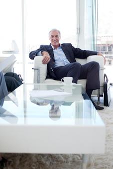 Старший бизнесмен в ожидании расслабляющий