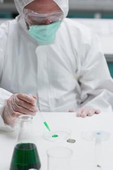 Химик в защитном костюме, добавляющий зеленую жидкость в чашку петри