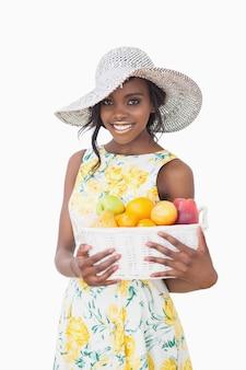 果物とボックスを保持する太陽の帽子を持つ女性