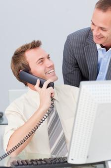 オフィスで同僚と話す電話でビジネスマン