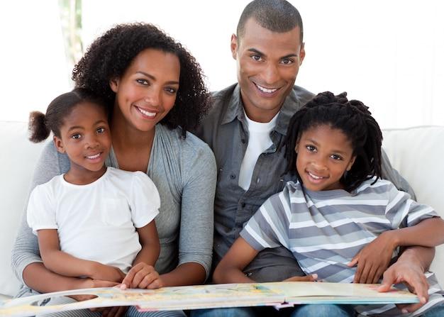 Портрет афро-американской семьи, читающей книгу в гостиной