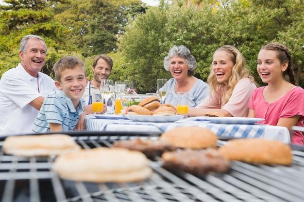 Смеющаяся семья с барбекю в парке вместе