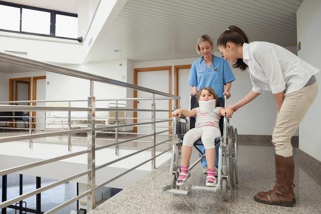 母親と一緒に車椅子で子供を押している看護師