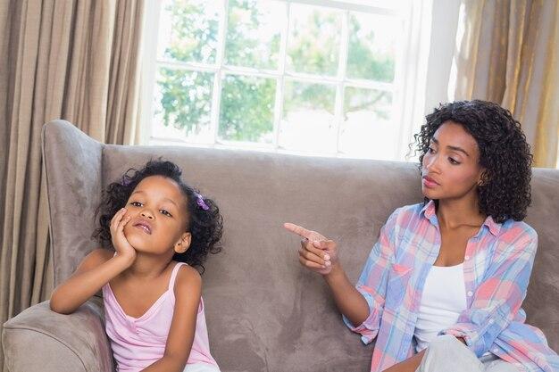 彼女の娘をソファーで叱るかなりの母親