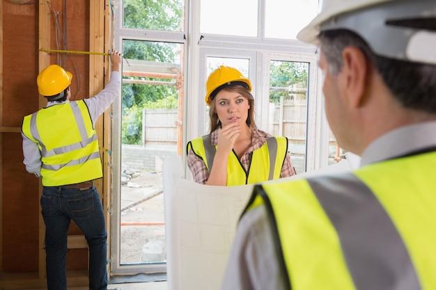 女性と建築家は木製のフレームを測定しながら男が話している