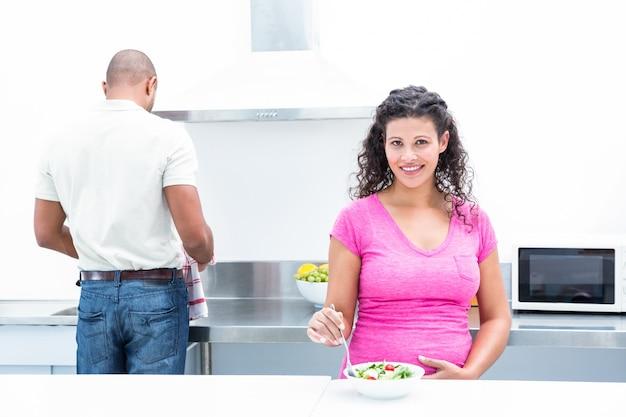 キッチンで助けている夫と幸せな妻の肖像