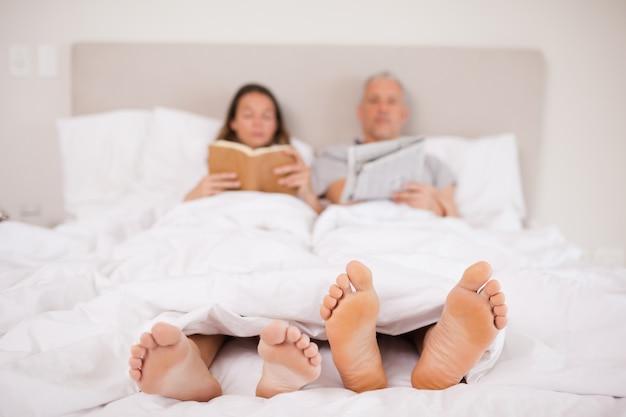 Женщина читает книгу, пока ее спутник читает новости