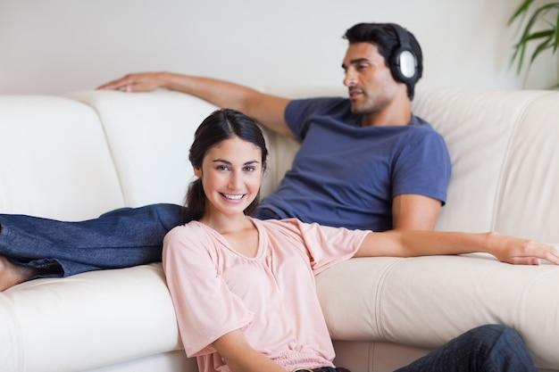 Молодая женщина, ставит, пока ее муж слушает музыку